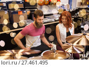 Купить «happy man and woman playing cymbals at music store», фото № 27461495, снято 11 декабря 2014 г. (c) Syda Productions / Фотобанк Лори