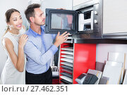 Купить «Smiling family couple choosing new microwave», фото № 27462351, снято 15 июня 2017 г. (c) Яков Филимонов / Фотобанк Лори