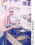 Купить «young woman picking dried beans in store», фото № 27464423, снято 15 ноября 2018 г. (c) Яков Филимонов / Фотобанк Лори