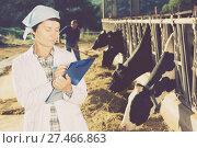 Купить «Adult woman is standing in uniform and checking the quality of milk», фото № 27466863, снято 24 октября 2017 г. (c) Яков Филимонов / Фотобанк Лори