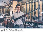 Brunette male hunter choosing shotgun in store. Стоковое фото, фотограф Яков Филимонов / Фотобанк Лори