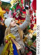 Купить «Happy girl choosing Christmas decoration at market», фото № 27506355, снято 18 февраля 2020 г. (c) Яков Филимонов / Фотобанк Лори