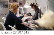 Купить «Nail master in medical mask doing professional manicure for white caucasian model, cosmetic salon», видеоролик № 27507515, снято 16 августа 2018 г. (c) Константин Шишкин / Фотобанк Лори