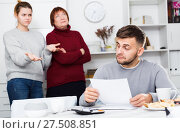 Купить «Frustrated man with papers on background with discontented family», фото № 27508851, снято 27 ноября 2017 г. (c) Яков Филимонов / Фотобанк Лори