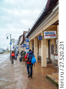 Купить «Zakopane, Poland - JAN 01, 2018: People go to the old bus terminal in  winter day», фото № 27520231, снято 1 января 2018 г. (c) Юлия Кузнецова / Фотобанк Лори