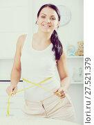 Купить «Woman measures waist by measuring tape», фото № 27521379, снято 7 декабря 2019 г. (c) Яков Филимонов / Фотобанк Лори
