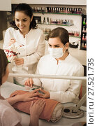 Manicurists choosing color of nail polish with client in nail salon. Стоковое фото, фотограф Яков Филимонов / Фотобанк Лори