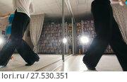 Купить «Young attractive man and woman dancing and rehearsing Latin American dance in costumes in the Studio, focus reflection in the mirroron and legs», видеоролик № 27530351, снято 7 августа 2020 г. (c) Константин Шишкин / Фотобанк Лори