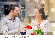 Купить «happy couple with present and flowers in mall», фото № 27534671, снято 10 ноября 2014 г. (c) Syda Productions / Фотобанк Лори