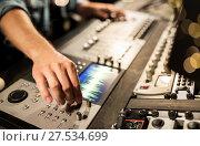 Купить «man using mixing console in music recording studio», фото № 27534699, снято 18 августа 2016 г. (c) Syda Productions / Фотобанк Лори