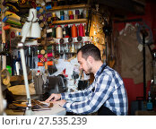 Купить «Adult man worker working on stitches for belt», фото № 27535239, снято 22 марта 2019 г. (c) Яков Филимонов / Фотобанк Лори