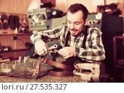 Купить «Smiling male worker shaping new hole in belt», фото № 27535327, снято 2 февраля 2017 г. (c) Яков Филимонов / Фотобанк Лори