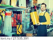Купить «Laughing guy deciding on best garden sprayer», фото № 27535391, снято 2 марта 2017 г. (c) Яков Филимонов / Фотобанк Лори