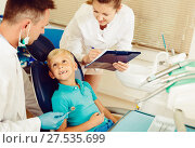 Купить «Dentist man is diagnosing the child while female assistant is writing down patient's complaint», фото № 27535699, снято 25 мая 2017 г. (c) Яков Филимонов / Фотобанк Лори