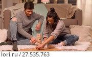 Купить «happy couple playing block-stacking game at home», видеоролик № 27535763, снято 23 января 2018 г. (c) Syda Productions / Фотобанк Лори