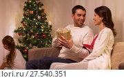 Купить «happy family with christmas present at home», видеоролик № 27540351, снято 17 января 2018 г. (c) Syda Productions / Фотобанк Лори