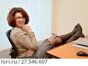 Купить «Веселая женщина сидит в офисе с ногами на столе и очками на колене», фото № 27546607, снято 3 февраля 2018 г. (c) Ирина Борсученко / Фотобанк Лори