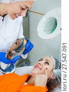 Купить «Woman client checking result of beauty procedures», фото № 27547091, снято 21 февраля 2019 г. (c) Яков Филимонов / Фотобанк Лори