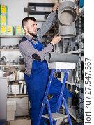 Купить «Young smiling guy worker choosing drain pipe detail», фото № 27547567, снято 15 марта 2017 г. (c) Яков Филимонов / Фотобанк Лори