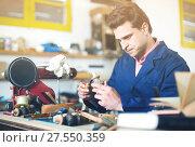 Купить «Craftsman in uniform working in carpentry», фото № 27550359, снято 8 апреля 2017 г. (c) Яков Филимонов / Фотобанк Лори