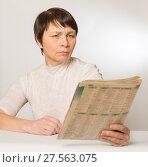 Купить «Пресбиопия. Женщина читает газету на вытянутой руке», фото № 27563075, снято 5 февраля 2018 г. (c) Юлия Бабкина / Фотобанк Лори