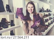 Купить «Smiling girl is demonstraiting autumn shoes», фото № 27564211, снято 13 декабря 2017 г. (c) Яков Филимонов / Фотобанк Лори