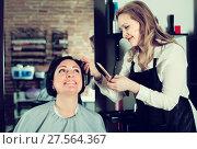 Купить «Young haircut master is doing hairstyle and cut by means of scissors», фото № 27564367, снято 7 марта 2017 г. (c) Яков Филимонов / Фотобанк Лори