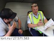 Купить «Инспектор дорожно-патрульной службы полиции оформляет протокол о нарушении правил дорожного движения», фото № 27571583, снято 3 августа 2017 г. (c) Free Wind / Фотобанк Лори