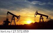 Купить «Working oil pumps silhouette against sunset», видеоролик № 27572059, снято 19 октября 2017 г. (c) Михаил Коханчиков / Фотобанк Лори