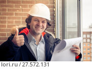 A handsome construction worker giving a thumbs-up sign. Authentic construction worker on actual construction site. Soft focus, toned. Стоковое фото, фотограф Marina Sharova / Фотобанк Лори
