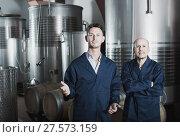 Купить «Two men in uniforms standing in winery fermentation compartment», фото № 27573159, снято 13 декабря 2019 г. (c) Яков Филимонов / Фотобанк Лори