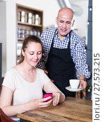 Купить «Young waiter brought coffee to a girl», фото № 27573215, снято 22 апреля 2017 г. (c) Яков Филимонов / Фотобанк Лори