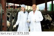 Купить «Farm employees standing near milking herd», фото № 27573335, снято 17 июня 2019 г. (c) Яков Филимонов / Фотобанк Лори