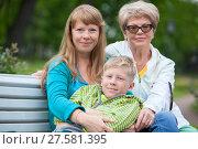 Купить «Мама и бабушка обнимают мальчика, сидя на скамейке в парке», фото № 27581395, снято 8 июня 2017 г. (c) Кекяляйнен Андрей / Фотобанк Лори