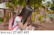 Купить «An philippine schoolgirl girl with a backpack is sitting and crying near the tropical coast. Sad mood.», видеоролик № 27607431, снято 25 января 2018 г. (c) Mikhail Davidovich / Фотобанк Лори