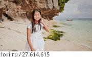 Купить «A charming and happy philippine teenage girl in a white summer dress is running along a tropical beach near the rocks. She is happily spinning. Childhood. Recreation.», видеоролик № 27614615, снято 25 января 2018 г. (c) Mikhail Davidovich / Фотобанк Лори