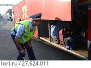 Купить «Инспектор дорожно-патрульной службы полиции проверяет багажный отсек междугороднего пассажирского автобуса», фото № 27624011, снято 3 августа 2017 г. (c) Free Wind / Фотобанк Лори