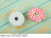 Купить «Two round glazed donut on blue painted wood», фото № 27637027, снято 20 июля 2019 г. (c) PantherMedia / Фотобанк Лори