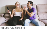 Купить «Young couple sitting on sofa quarreling because of TV remote control», видеоролик № 27660315, снято 17 октября 2017 г. (c) Яков Филимонов / Фотобанк Лори