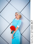 Купить «Daring blonde rebel with brightly painted lips. In a long blue dress with bouquet of red in hand. Against the background of the rectangular decorative walls.», фото № 27660467, снято 22 июня 2018 г. (c) PantherMedia / Фотобанк Лори