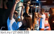 Купить «Group of smiling people clubbing in the night club with drinks», видеоролик № 27660555, снято 7 сентября 2017 г. (c) Яков Филимонов / Фотобанк Лори