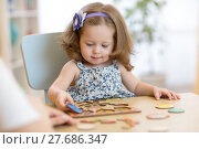 Купить «Small toddler or baby kid playing with puzzle shapes on low table in children room in nursery or preschool.», фото № 27686347, снято 7 июня 2020 г. (c) Оксана Кузьмина / Фотобанк Лори