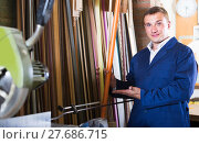 Купить «portrait of man in uniform choosing framing moulding in studio», фото № 27686715, снято 19 января 2019 г. (c) Яков Филимонов / Фотобанк Лори