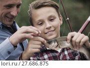 Купить «teenager boy holding catch fish on hook», фото № 27686875, снято 21 января 2020 г. (c) Яков Филимонов / Фотобанк Лори