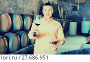 Купить «Owner of winery standing with wine in cellar», фото № 27686951, снято 22 сентября 2016 г. (c) Яков Филимонов / Фотобанк Лори