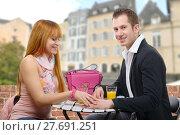 Купить «Cheerful young couple sitting in a coffee shop terrace», фото № 27691251, снято 20 июня 2019 г. (c) PantherMedia / Фотобанк Лори