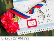 Купить «23 февраля, открытка на день защитника Отечества. Красная гвоздика, российский флаг и календарь с датой 23 февраля на камуфляжном фоне», фото № 27704795, снято 10 апреля 2017 г. (c) Зезелина Марина / Фотобанк Лори