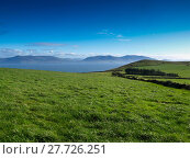 Купить «View from the Dingle Peninsula to the Iveragh peninsula with green grass, a blue ridge and a clear blue sky.», фото № 27726251, снято 19 апреля 2019 г. (c) PantherMedia / Фотобанк Лори