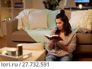 Купить «happy young woman reading book at home», фото № 27732591, снято 13 января 2018 г. (c) Syda Productions / Фотобанк Лори