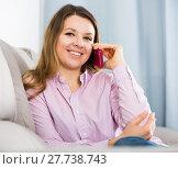 Купить «Young female is sitting and using her phone», фото № 27738743, снято 13 марта 2017 г. (c) Яков Филимонов / Фотобанк Лори